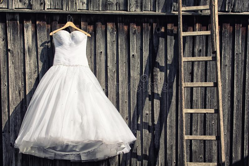 Wedding dress. In front of an old wooden wall stock photography
