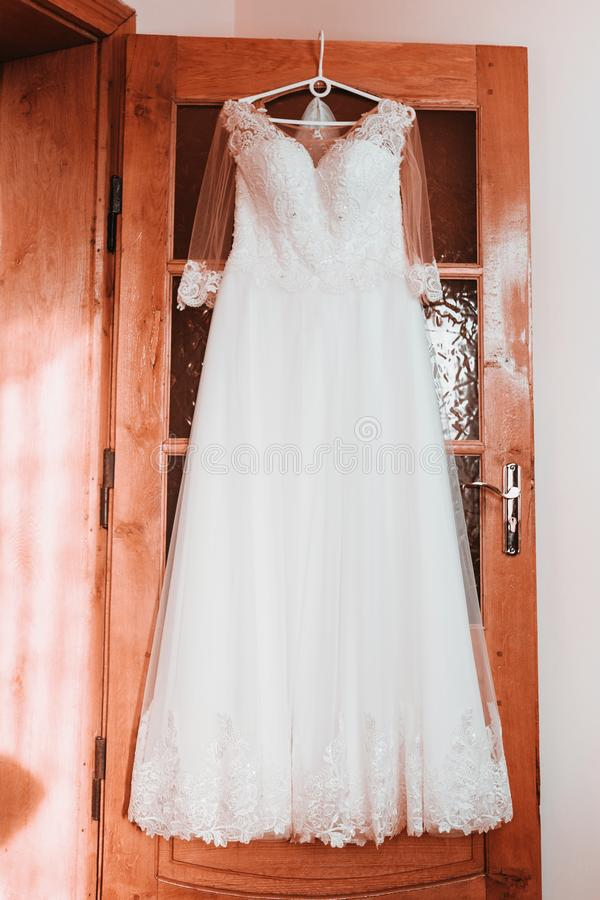 Wedding dress on hanger on a wall, Beautiful gown stock photography