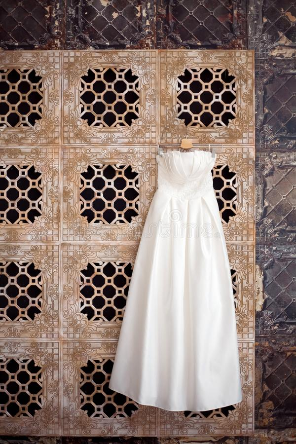Wedding dress hanging in anticipation of the bride. Beautiful interior. White dress stock photos
