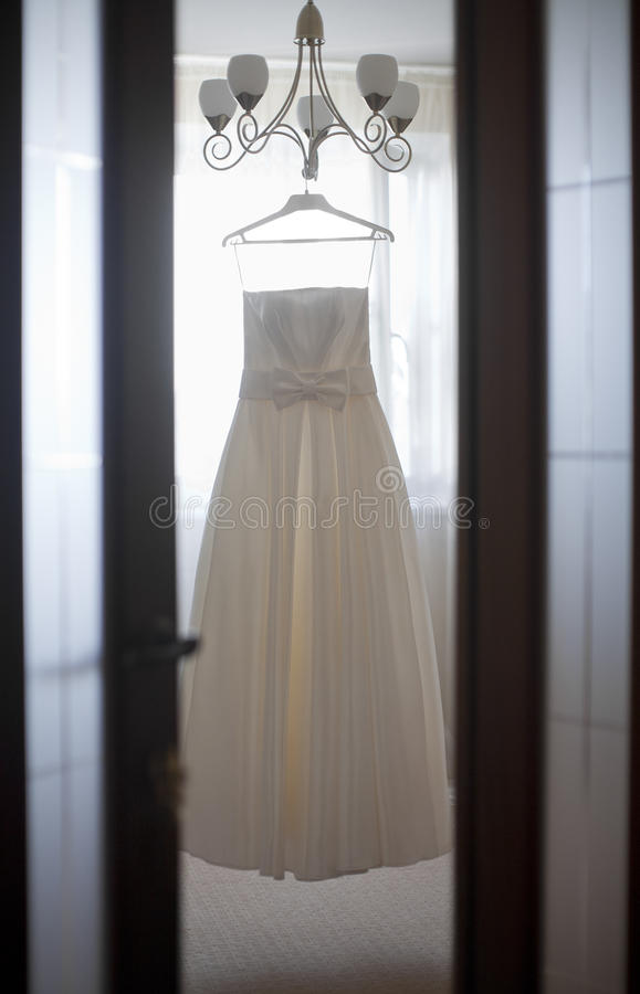 Wedding dress hanging on the chandelier. In the room stock photo