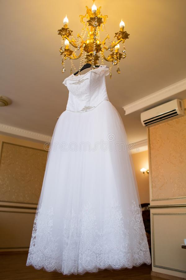 Wedding dress hanging on the chandelier. bride accessories. charges of the bride. bride`s morning.  stock image