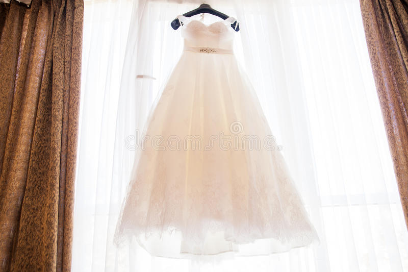 Wedding dress hanging on the chandelier in the room. Wedding dress belt hanging on the chandelier in the room stock images