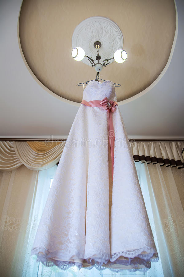 Wedding dress hanging on the chandelier in the room. Wedding dress with peach belt hanging on the chandelier in the room royalty free stock photo
