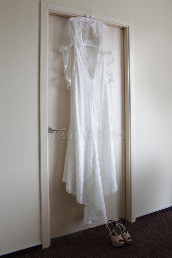 Wedding dress hanging on the door, shoes stand on the floor stock image
