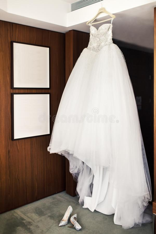 Wedding dress hanging in the room and shoes on a gray floor royalty free stock images