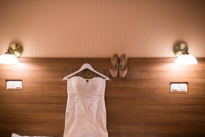 Wedding dress hanging on the wall in the room and bridal beige shoes. Image of the bodice of a beige wedding dress on a wooden whi royalty free stock photos
