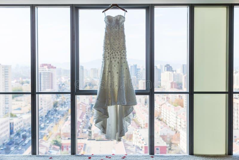 Wedding dress. Hanging on the window stock photography