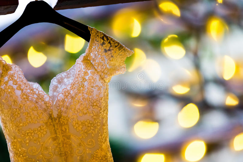 Wedding dress. Part of wedding dress hanging on the window royalty free stock photo