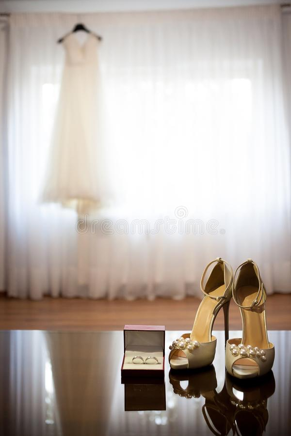 Wedding dress and shoes in a room. Wedding day and preparation stock image