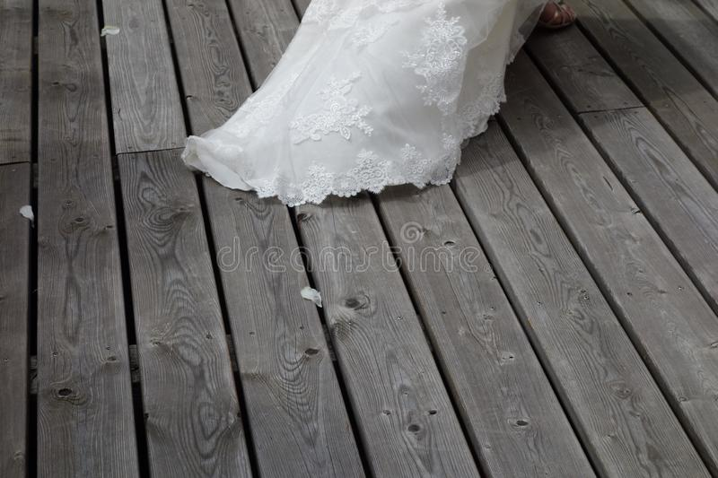 Wedding dress stitch on a wooden floor. Lacy sliver of wedding dress leaving bride royalty free stock images