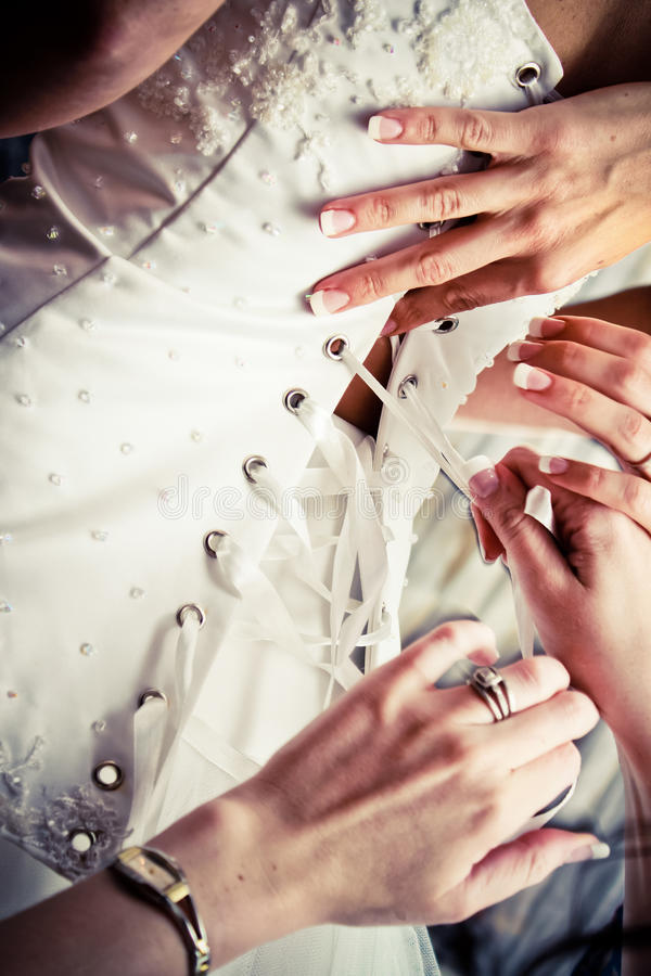 Wedding Dress Time. A wedding dress needs to sit perfect on that day. Always with the help of a bride's bridesmaids. Pulling the top piece of the dress with a royalty free stock photos