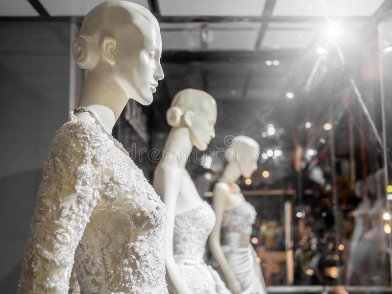 Wedding dress. White female mannequin in wedding dress in showcase. Bridal dresses on the mannequins in wedding window display with light on wedding suit shop stock image
