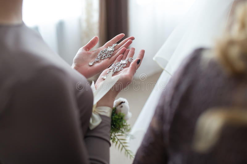 Wedding earrings on a female hand stock photography