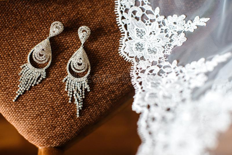 Wedding earrings and veil on the chair stock image