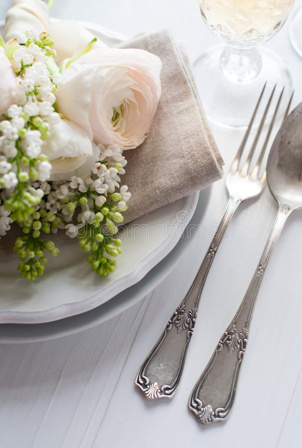 Wedding elegant dining table setting. Festive wedding elegant dining table setting with a bouquet of flowers, buttercups and white lilac, and vintage cutlery on royalty free stock photos
