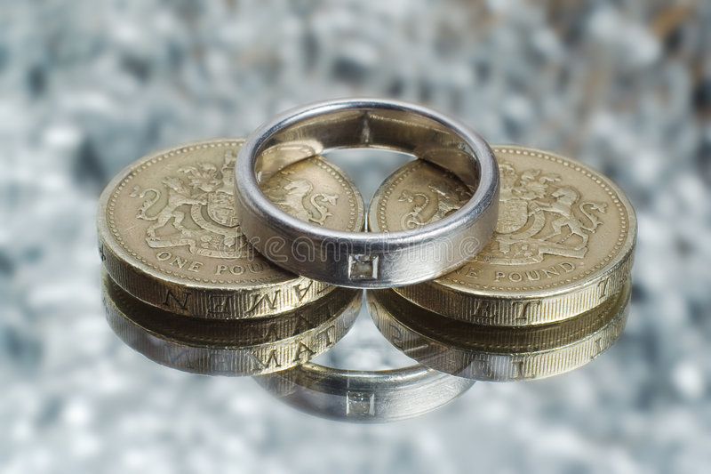 Wedding expense. Coins and wedding ring, to represent the costs and expenses involved in marriage stock photo