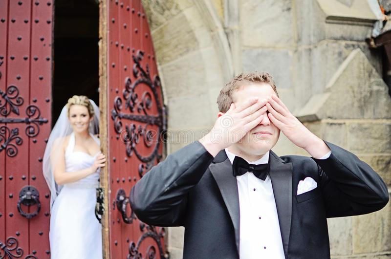 Wedding first look. A groom covering his eyes with his bride behind him