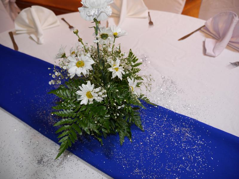 Wedding floral arrangement. Beautiful centerpiece of a bouquet of white flowers and green ferns with a spray of silver dust on the table stock image