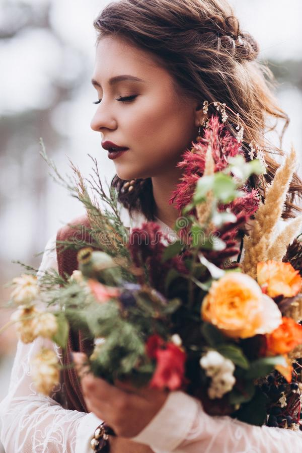 Wedding floristry in a yellow autumn meadow in the hands of a girl dressed in the style of boho. royalty free stock photography