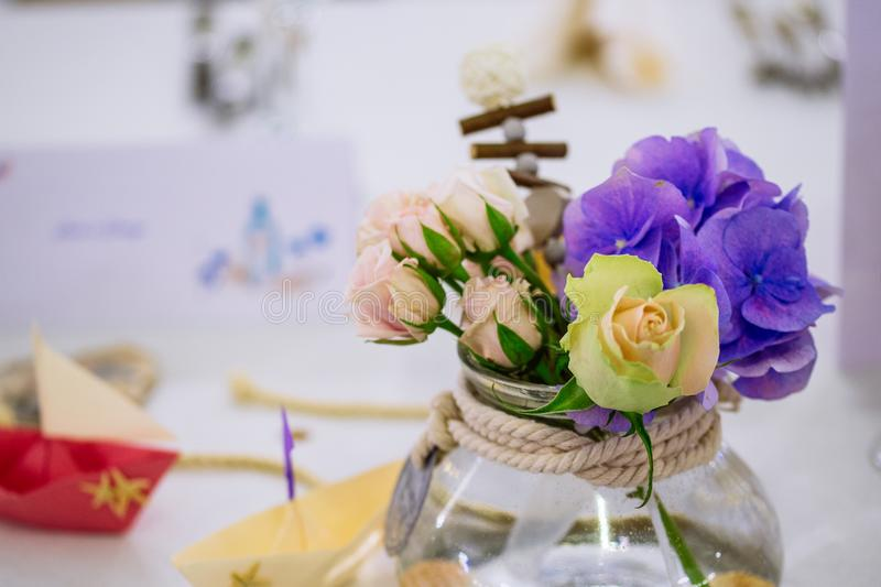 Wedding flower bouquet in glass vase on guest table. Mixed flower bouquet in glass vase on guest table, marine nautical theme wedding stock images