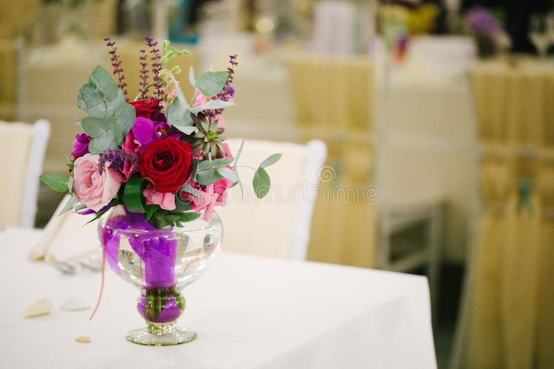 Wedding flower bouquet in glass vase on guest table. Restaurant party stock photography