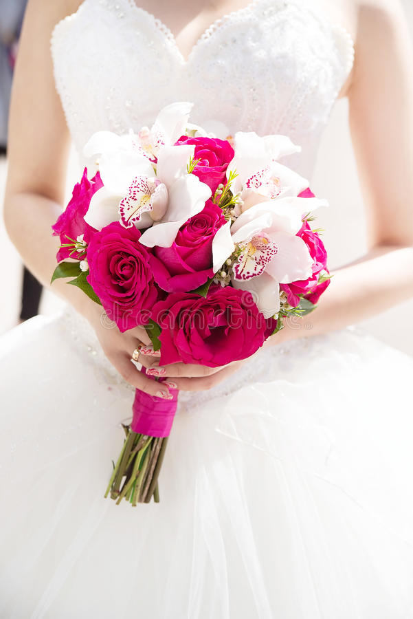 Wedding flower bouquet with pink roses and white callas. In hand stock image