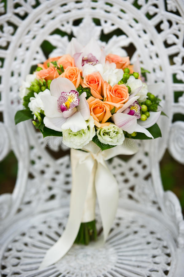 Wedding flower bouquet on a white garden chair royalty free stock image