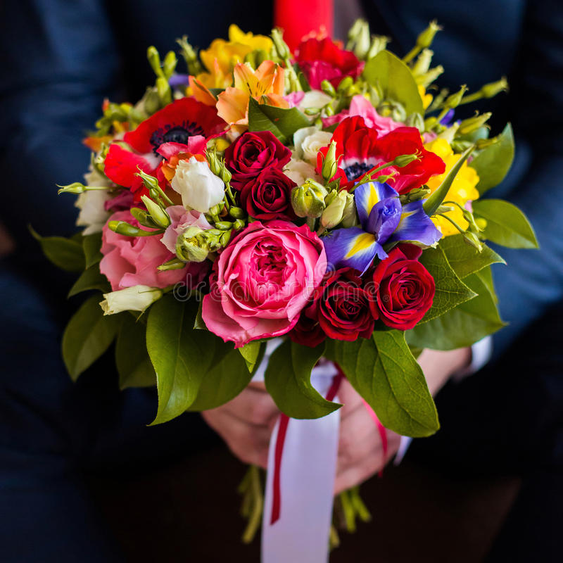 Wedding flowers, groom holds bouquet of white, blue, yellow flowers and red roses stock images