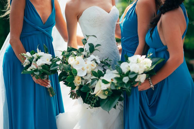 Wedding flowers in hand the bride and her bridesmaids stock image