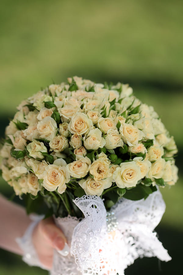 Wedding flowers in hand. Closeup view of one beautiful fresh bright white yellow big wedding bouquet of rose flowers in hand of bride in white dress, vertical stock images