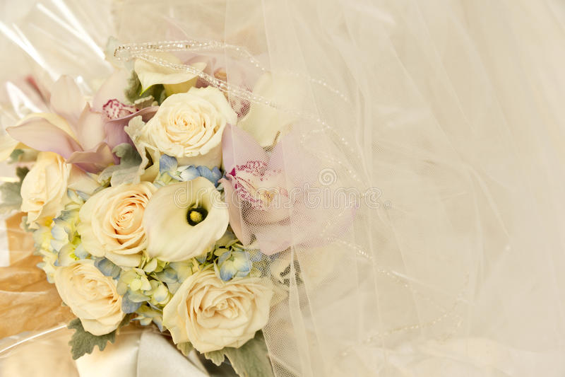 Wedding flowers and ivory bridal veil stock photos