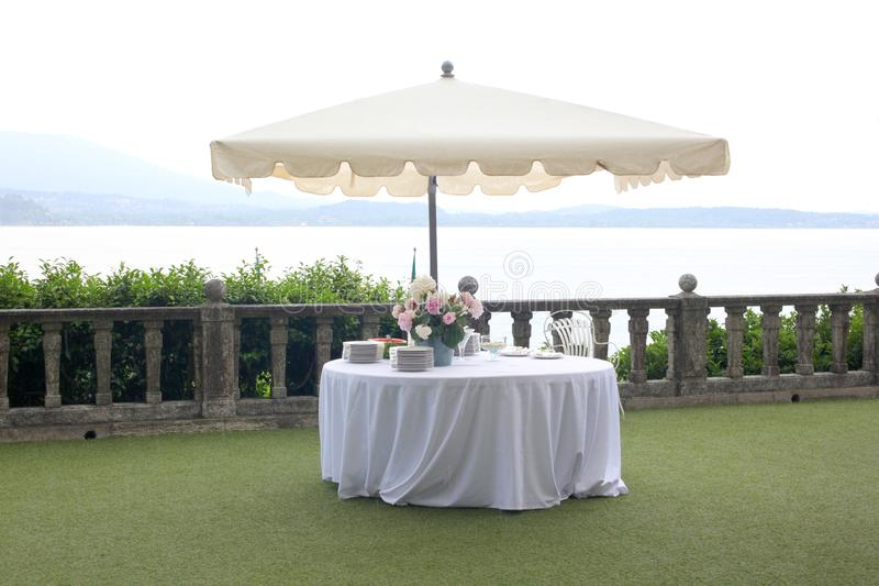 Wedding garden party set: white table and sun umbrella in an elegant garden ready for the party with copy space for your text. Wedding garden party set: white royalty free stock photography