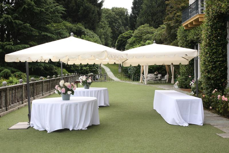 Wedding garden party set: white table and sun umbrella in an elegant garden ready for the party with copy space for your text. Wedding garden party set: white royalty free stock photos