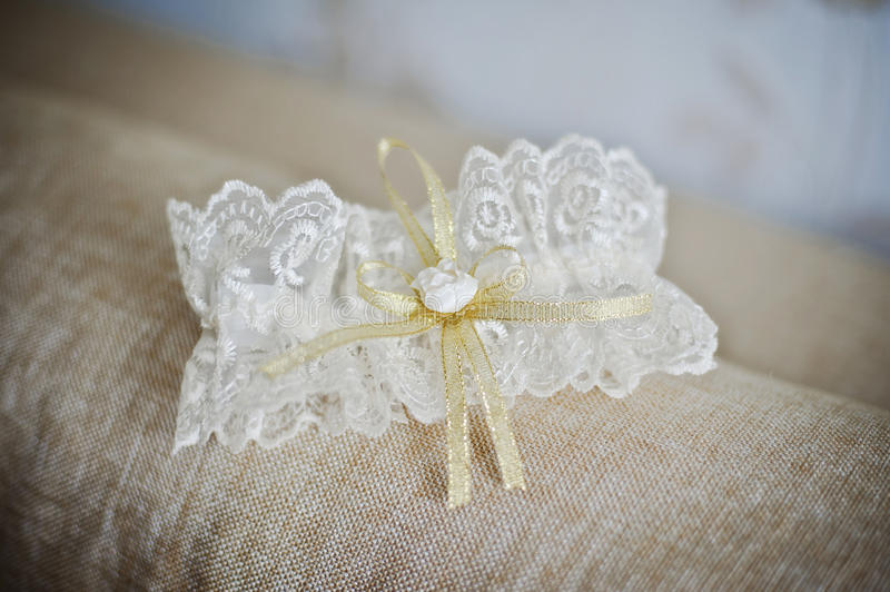 Wedding garter. Beautiful white lace wedding garter with golden ribbons stock photography