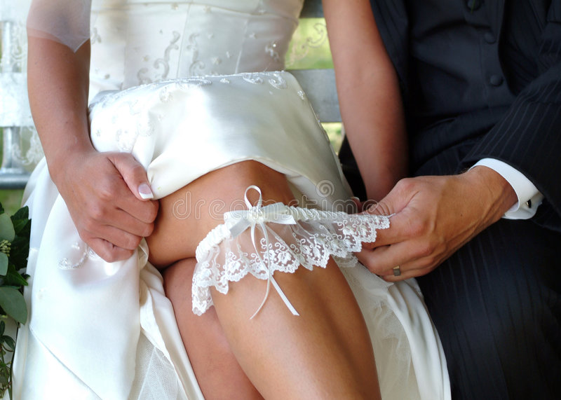 Wedding garter. Bride's gown pushed up to her knee, showing garter pulled by groom's hand stock photo
