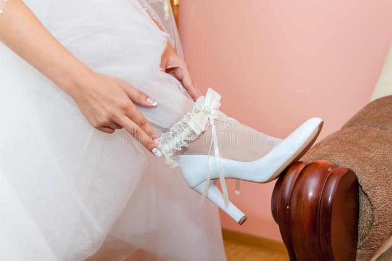 Wedding garter on the bride`s leg. Garter on the leg of a bride, slim bride in wedding luxury dress showing her silk garter with golden ribbon. woman have a stock images