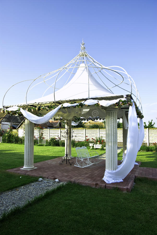 Wedding gazebo. Arrangement with flowers and rocking chair stock photos