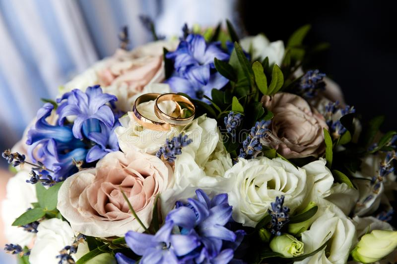 Wedding gold rings on a bouquet of flowers royalty free stock images