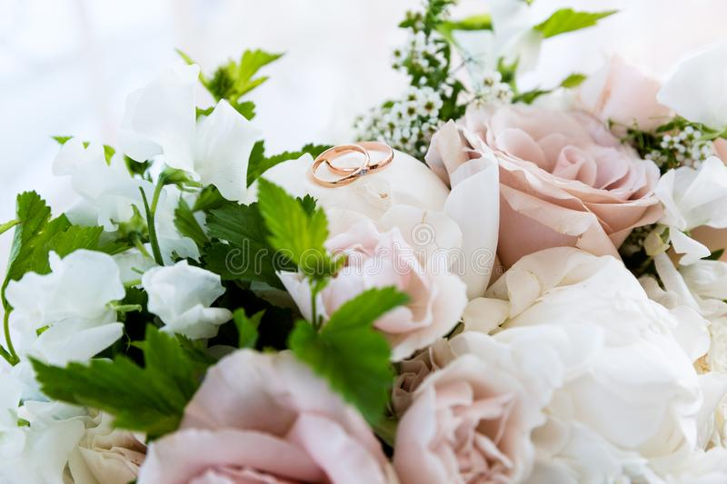 Wedding gold rings on a bouquet of flowers royalty free stock photos