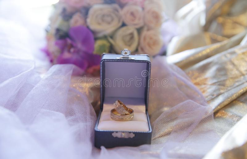 Wedding gold rings in a box on a golden fabric with a veil and bouquet of flowers. Luxury. stock photos
