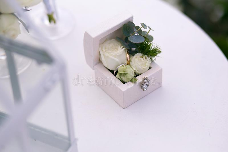 Wedding gold rings decorated with flowers on a white background in a wooden box on the table for a wedding ceremony stock images