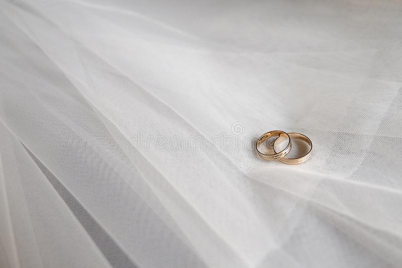 Wedding gold rings with precious stones on the bride`s veil stock image