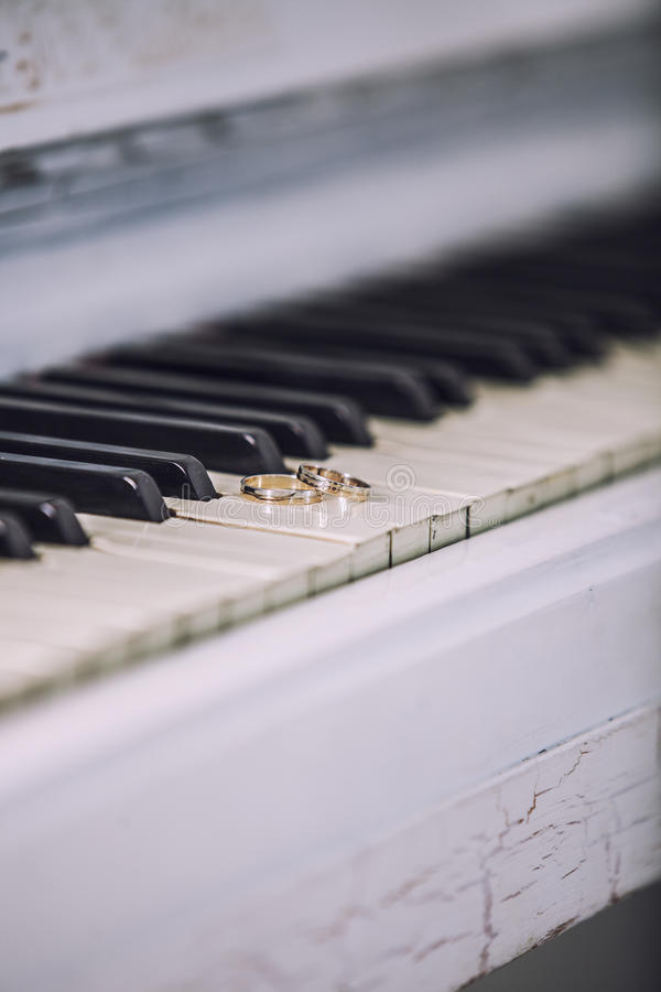 Wedding gold rings on the white keys of the piano. Ceremony, religion, music, vintage, custom, decoration stock photography