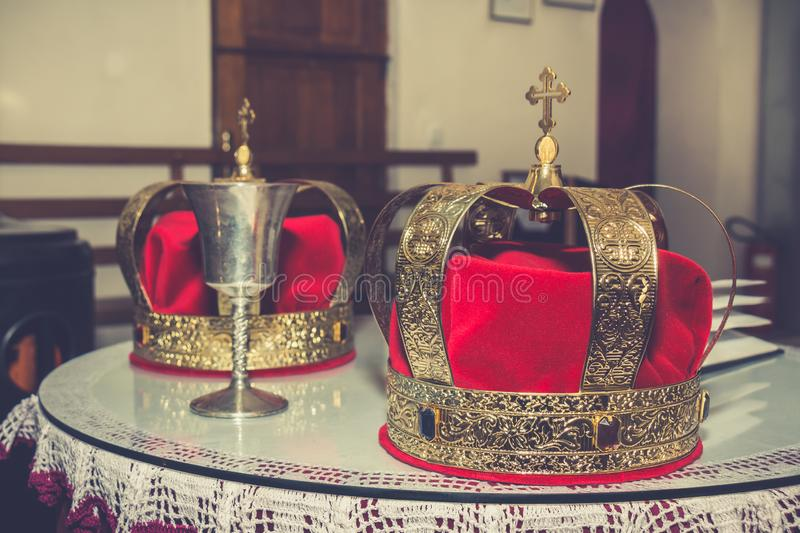 Wedding golden crowns and chalice. Wedding golden crowns and ancient chalice ready for wedding ceremony in Serbian orthodox church royalty free stock image