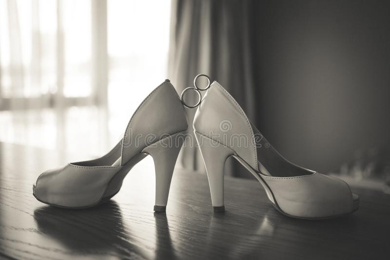Wedding rings between bride`s pink shoes. Ceremony. Wedding golden rings between bride`s pink shoes. Ceremony. Black and white royalty free stock image