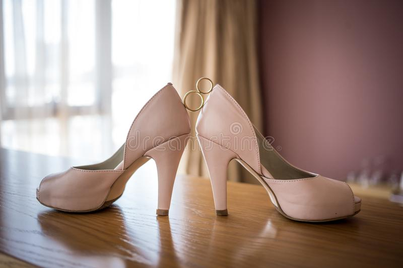 Wedding rings between bride`s pink shoes. Ceremony. Wedding golden rings between bride`s pink shoes. Ceremony stock photo