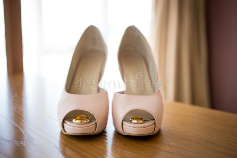 Wedding rings inside bride`s pink shoes. Ceremony. Wedding golden rings inside bride`s pink shoes. Ceremony royalty free stock photo