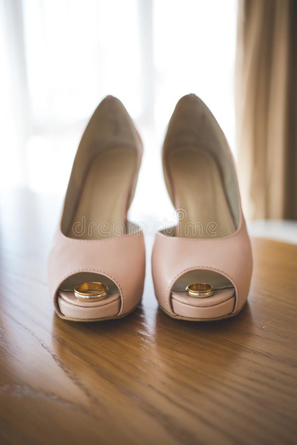 Wedding rings inside bride`s pink shoes. Ceremony. Wedding golden rings inside bride`s pink shoes. Ceremony. Vertical royalty free stock photos