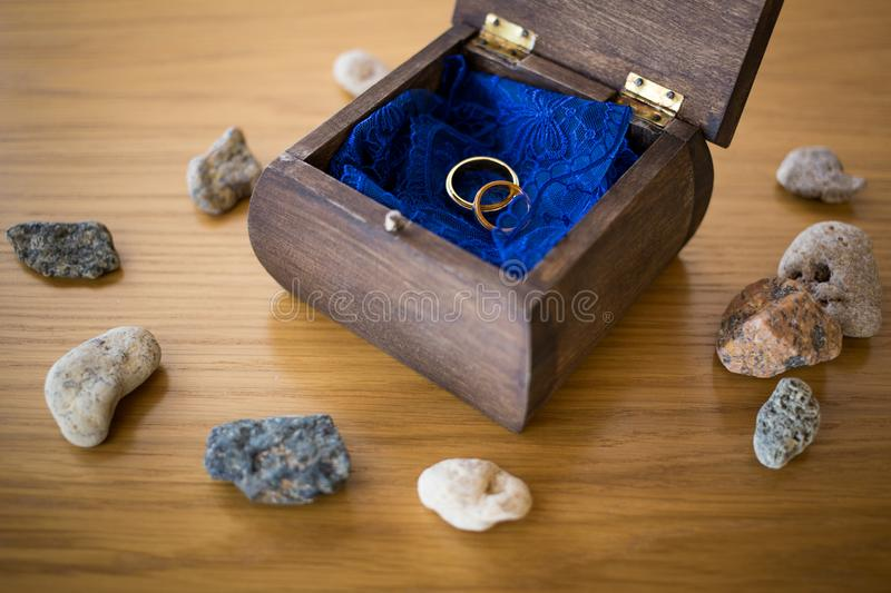 Wedding rings inside the open wooden box with stones around. Ceremony stock images