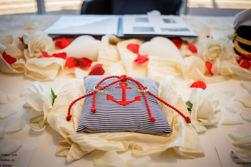 Wedding rings together with red rope on striped pillow with anchor on it. Marriage ceremony stock image